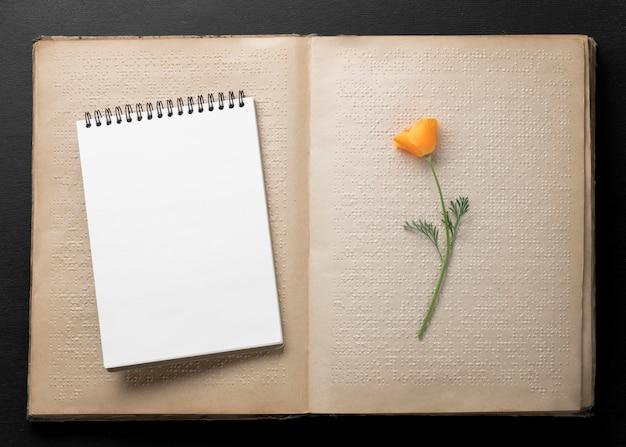 Bovenaanzicht oud brailleboek met bloem