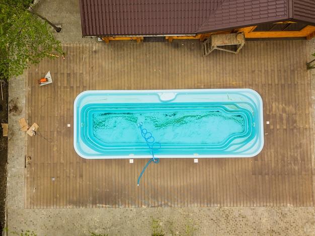 Bovenaanzicht oud vuil blauw zwembad zorg voor buitenzwembaden