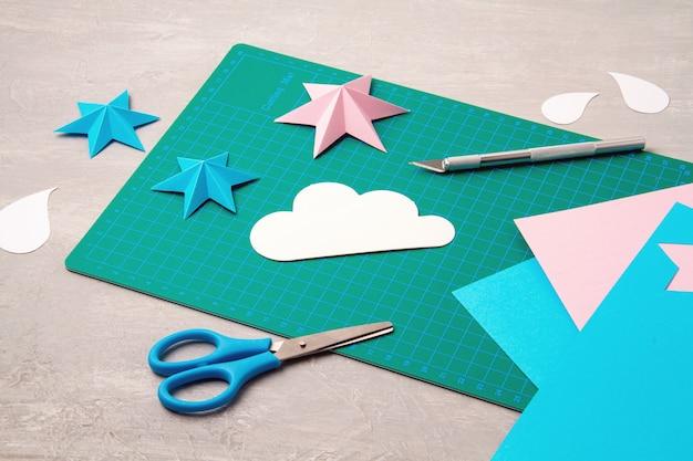 Bovenaanzicht over papier gesneden gereedschappen, schaar, snijder, snijmat en bewerkte papieren objecten. diy trendy projectconcept