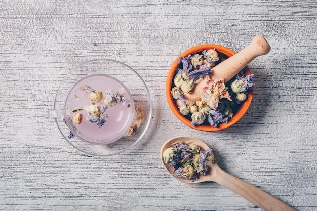 Bovenaanzicht paars gekleurd water in de beker met gedroogde bloem thee in een kom en lepel op witte houten achtergrond. horizontaal