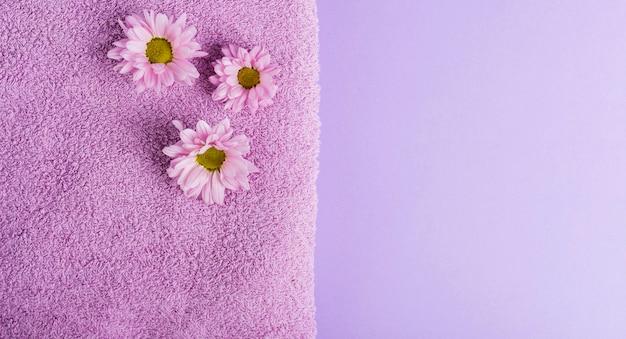 Bovenaanzicht paarse bloemen en handdoek met kopie-ruimte