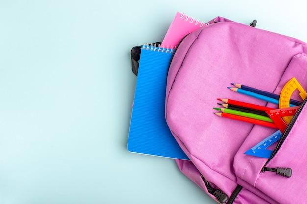 Bovenaanzicht paarse tas met voorbeeldenboeken en potloden op blauw bureau