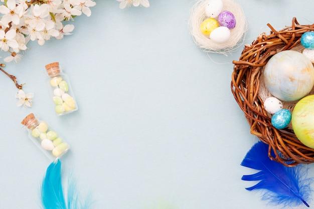 Bovenaanzicht paaseieren in nest en glazen flessen op een blauwe achtergrond met bloesem bloemen. kopieer ruimte voor tekst.