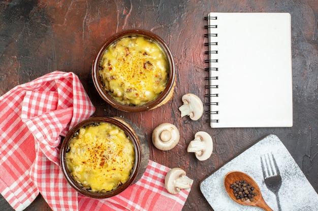 Bovenaanzicht paddenstoel met mosarella in kommen zwarte peper in houten lepel paddenstoelen notitieboekje op donkerrode tafel