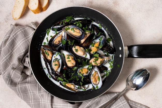 Bovenaanzicht pan met saus en mosselen