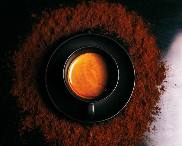 Bovenaanzicht pannenkoek in ronde metalen pan rond chocoladepoeder op het donkere oppervlak