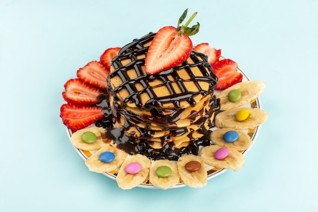 Bovenaanzicht pannenkoeken lekker heerlijk met gesneden rode aardbeien en bananen in witte plaat op het ijsblauw