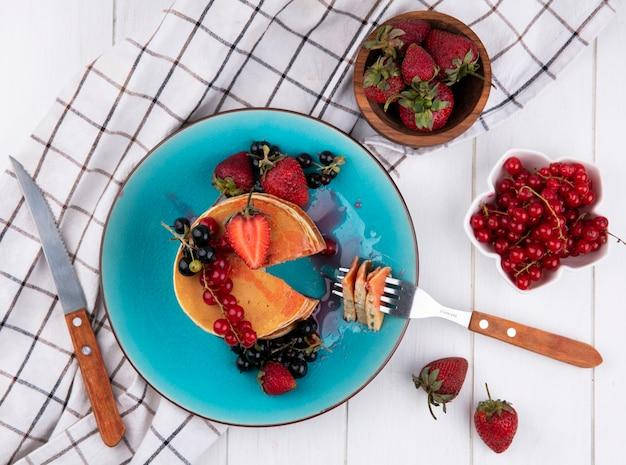 Bovenaanzicht pannenkoeken met aardbeien van zwarte en rode aalbessen met een vork en een mes op een plaat op een witte geruite handdoek