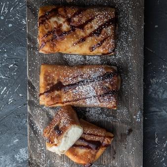 Bovenaanzicht pannenkoeken met chocoladesiroop en kwark en poedersuiker in snijplank