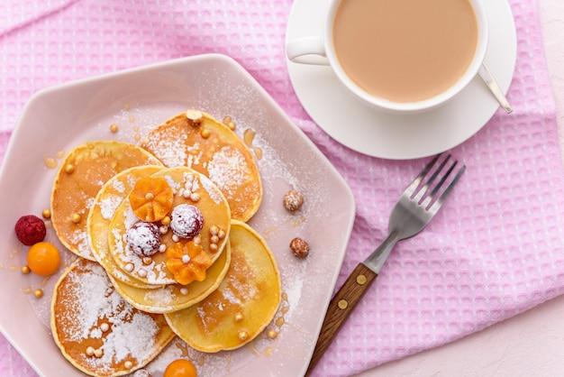 Bovenaanzicht pannenkoeken met frambozen, physalis en honing op roze bord, bestrooid met poedersuiker, met vork en kopje thee of koffie op roze theedoek