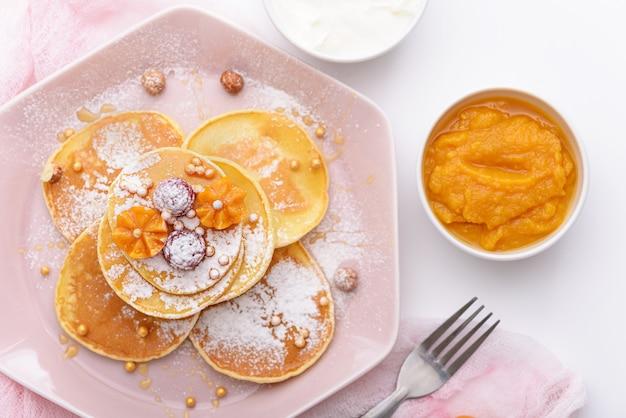 Bovenaanzicht pannenkoeken met frambozen, physalis en honing op roze plaat, bestrooid met poedersuiker, met vork, mango jam, zure room op witte achtergrond