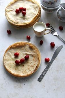 Bovenaanzicht pannenkoeken met gecondenseerde melk en kornoelje
