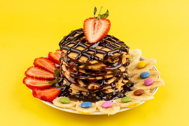 Bovenaanzicht pannenkoeken met gesneden rode aardbeien en bananen in plaat op de gele