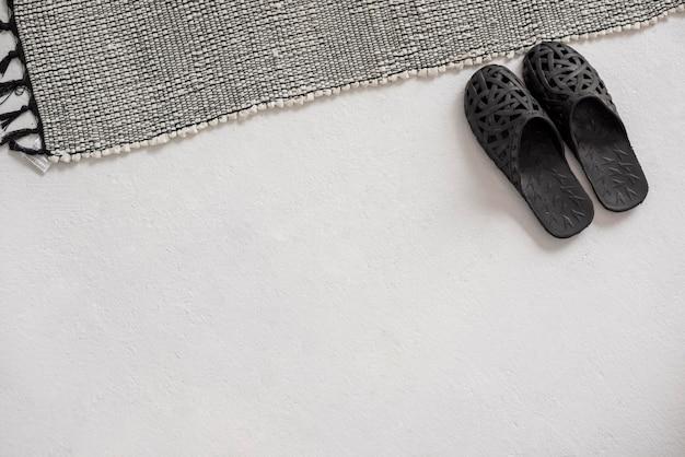 Bovenaanzicht pantoffels in de buurt van tapijt