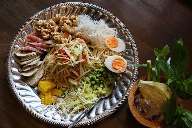 Bovenaanzicht papajasalade of som tum in thais eten met zuur varkensvlees, gekookt ei.