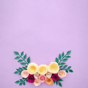 Bovenaanzicht papier bloemen en bladeren op paarse achtergrond