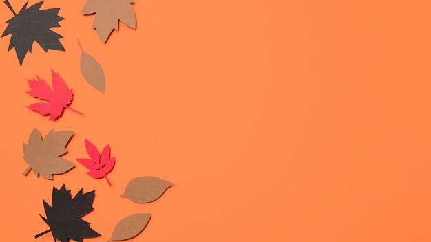 Bovenaanzicht papier herfstbladeren op oranje achtergrond met kopie ruimte