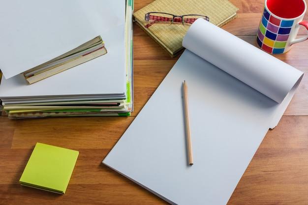 Bovenaanzicht, papier, notitieboeken, boeken op het bureau. tijd doorgebracht aan een heel lange tafel.