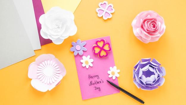 Bovenaanzicht papieren bloemen op gele achtergrond