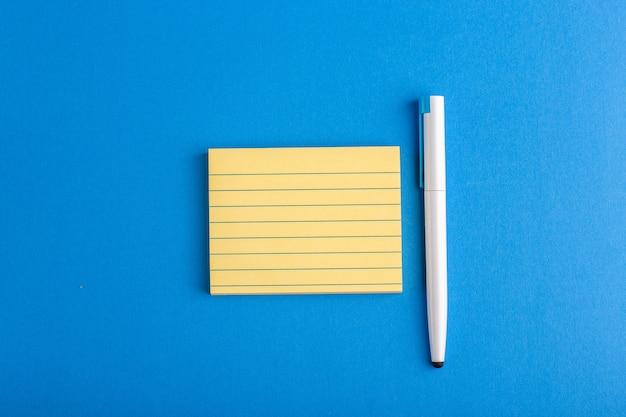 Bovenaanzicht papieren sticker met pen op blauwe ondergrond