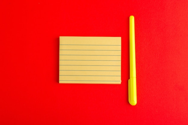 Bovenaanzicht papieren sticker met pen op rood oppervlak
