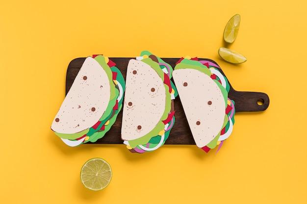 Bovenaanzicht papieren taco's op een houten bord