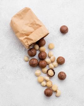 Bovenaanzicht papieren zak gevuld met macadamia noten en chocolade