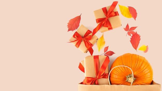Bovenaanzicht papieren zak met verse pompoen, geschenkdozen met herfstbladeren. winkelen voor halloween of thanksgiving. herfst concept. banier. plat leggen. ruimte kopiëren.