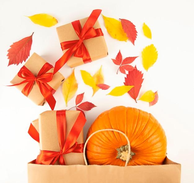 Bovenaanzicht papieren zak met verse pompoen, geschenkdozen met herfstbladeren. winkelen voor halloween of thanksgiving. herfst concept. plat leggen. ruimte kopiëren.