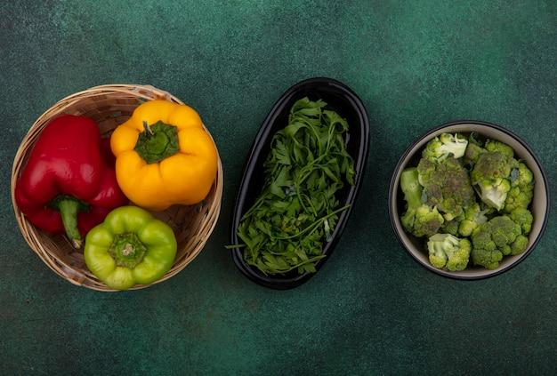 Bovenaanzicht paprika in een mand met kruiden en broccoli op een groene achtergrond