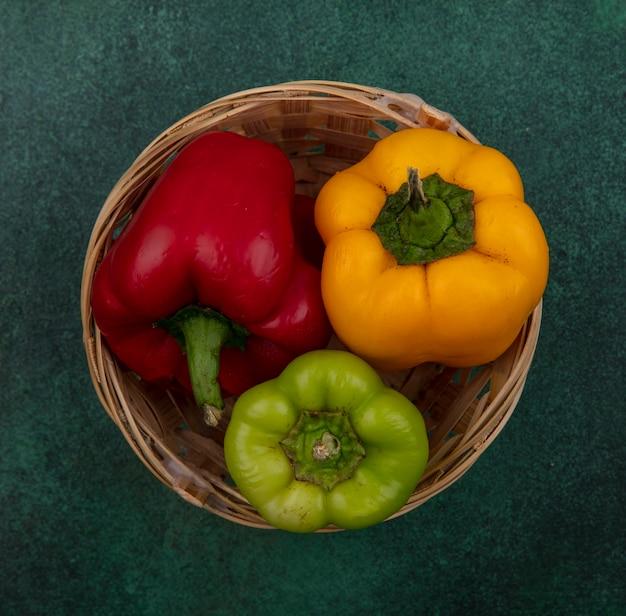Bovenaanzicht paprika in een mand op een groene achtergrond