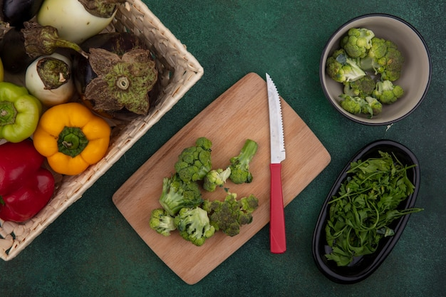Bovenaanzicht paprika met aubergines in een mand met broccoli op een snijplank met een mes op een groene achtergrond