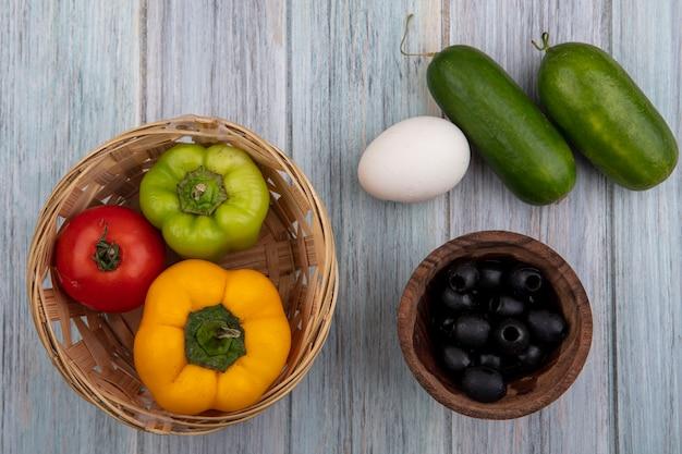 Bovenaanzicht paprika met tomaten kippenei olijven en komkommers op grijze achtergrond