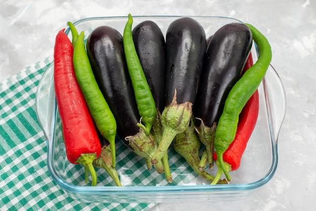 Bovenaanzicht paprika's en aubergines in transparante glazen kom op het heldere bureau voedsel maaltijd rauwe groente