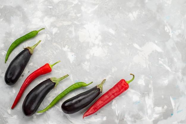 Bovenaanzicht paprika's en aubergines rijp en geïsoleerd op de witte achtergrond plantaardig voedsel rauw gerecht