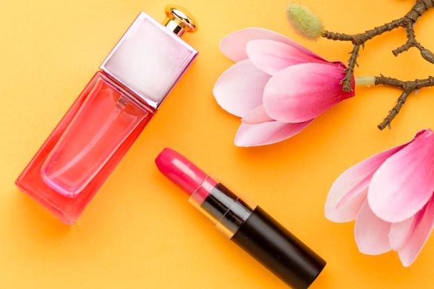 Bovenaanzicht parfum met lippenstift en bloemen