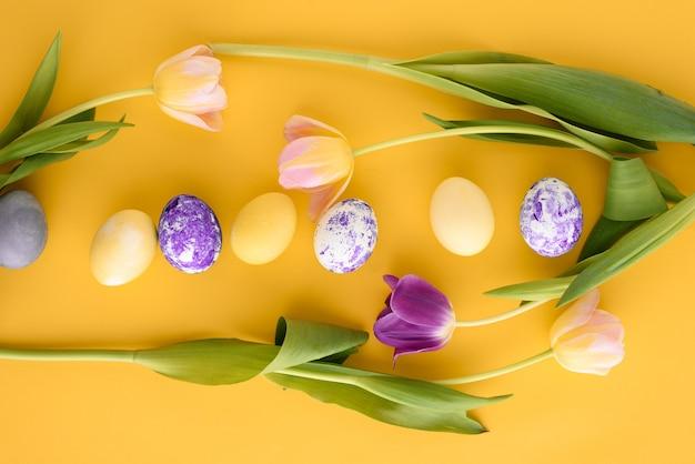 Bovenaanzicht pasen gele achtergrond met roze en paarse tulpen en paaseieren