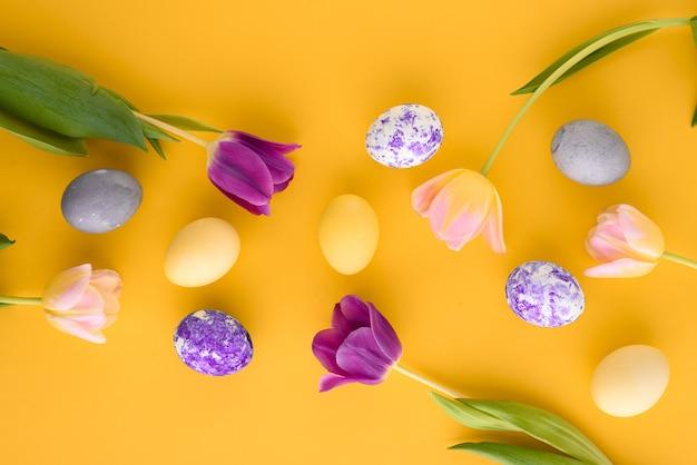 Bovenaanzicht pasen gele achtergrond met tulpen en paaseieren