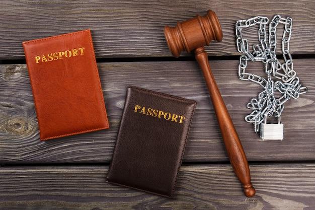 Bovenaanzicht paspoorten hamer en kettingen. immigratie probleem concept.
