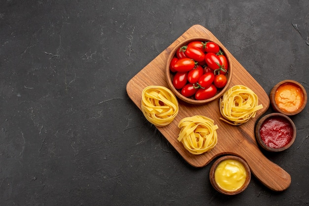 Bovenaanzicht pasta en sauzen tomaten en pasta op de snijplank en verschillende sauzen op de donkere achtergrond