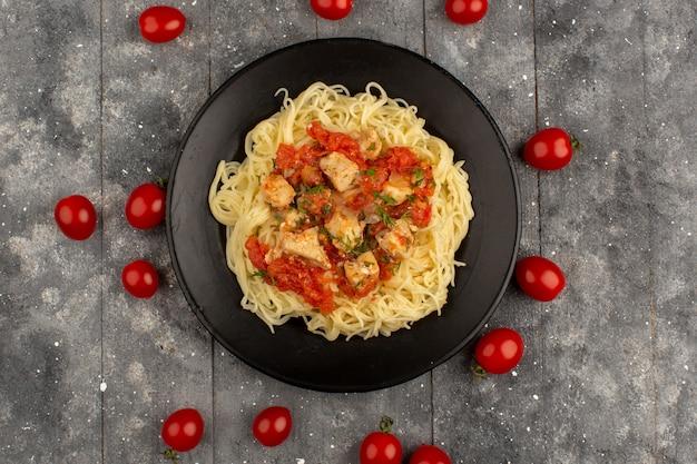 Bovenaanzicht pasta geel gekookt met kippenvleugels en tomatensaus in zwarte plaat op de grijze houten rustiek