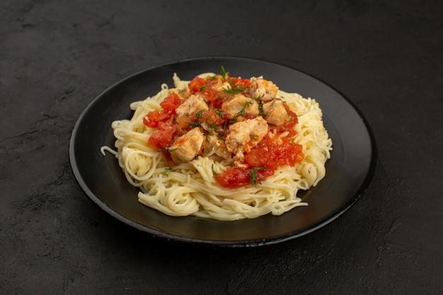 Bovenaanzicht pasta gekookt met kippenvleugels en tomatensaus in zwarte plaat op de donkere vloer