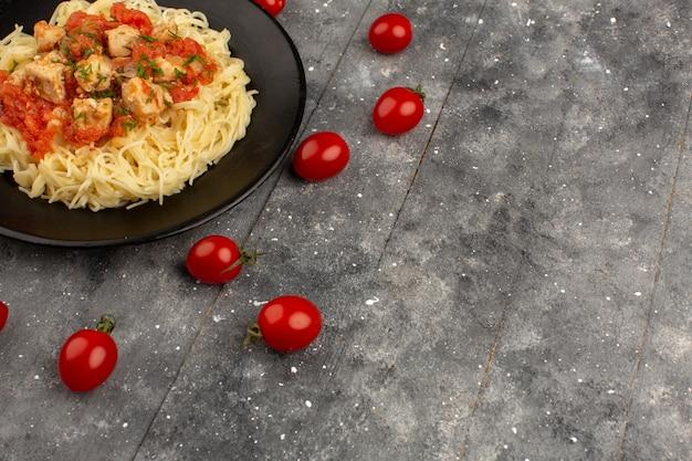 Bovenaanzicht pasta gekookt met kippenvleugels en tomatensaus in zwarte plaat op de grijze rustieke houten achtergrond