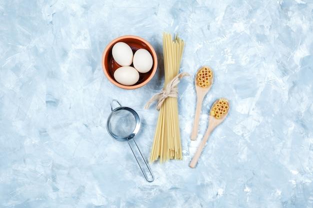 Bovenaanzicht pasta in houten lepels met eieren, zeef op grungy grijze achtergrond. horizontaal