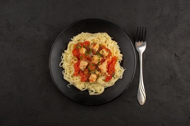 Bovenaanzicht pasta met kippenvleugels en tomatensaus in zwarte plaat op de donkere vloer