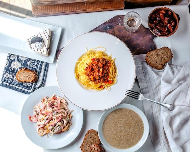 Bovenaanzicht pasta met verse salade en champignonsoep op het witte bureau