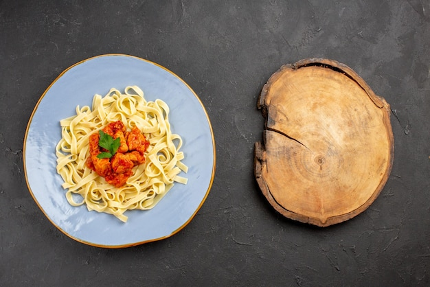 Bovenaanzicht pasta met vlees blauw bord smakelijke pasta met jus en vlees naast de houten snijplank op tafel