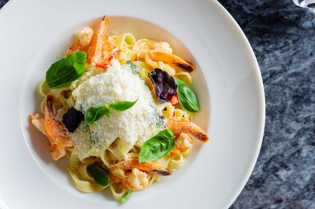 Bovenaanzicht pasta met zeevruchten, garnalen, basilicum en parmezaanse kaas op marmeren tafel. spaghetti in een witte kom. traditionele italiaanse keuken.