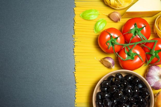 Bovenaanzicht: pasta of italiaanse spaghetti op zwarte steen leisteen achtergrond
