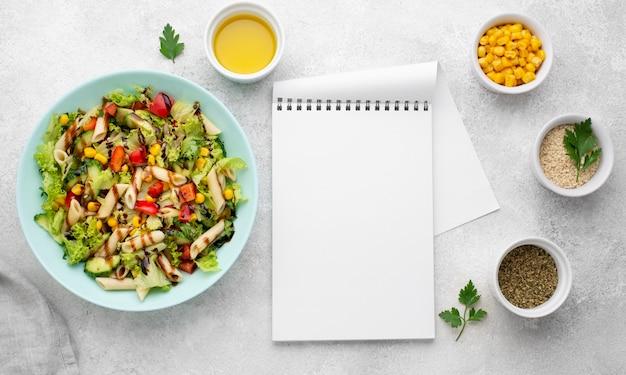 Bovenaanzicht pastasalade met balsamicoazijn en lege blocnote